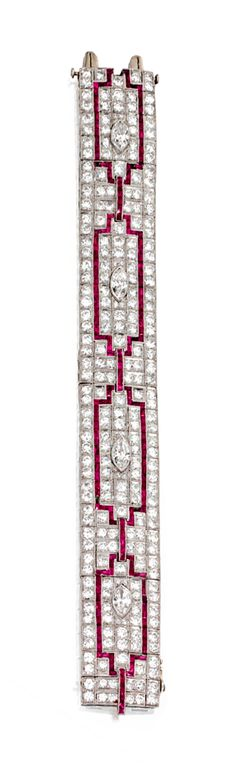 PLATINUM, DIAMOND AND RUBY BRACELET, CIRCA 1930.  The articulated strap set with 4 marquise-shaped diamonds weighing approximately 2.00 carats, and old European-cut and single-cut diamonds weighing approximately 19.20 carats, accented by a geometric pattern set with calibré-cut rubies, length 7 5/8  inches.