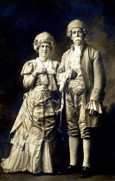 """Photograph of couple in 18th century """"fancy dress"""" - I get the outfits - sort of- but what's with the big white tache? Or is that foam from a Georgian cappuccino? Moustache Git!"""