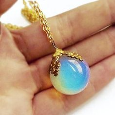 Opalite orb necklace on extra long gold tone chain. Very iridescent. The sphere is approximately 20mm.