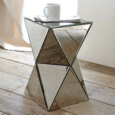 "From all angles. Whether you're going for old-Hollywood glamour or edgy, angular style, the Faceted Mirror Side Table's antiqued mirror surface reflects and refracts light, lightening up the look of any room.  12.5""sq. x 20.5""h.  West Elm  $199"