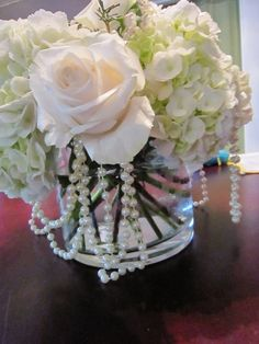 Centerpieces: I love how the flowers look in a small round vase and pearls hanging out