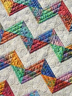 Love this and it is made with half square triangles, batiks and a neutral. The custom free motion quilting is amazing!