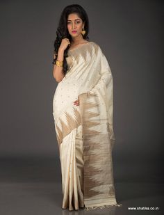 Crafted to sooth you but woo others, Suprabha Milky White Temple Bordered Pure Jute Silk Saree looks pristine and sublime in delicate cream with tiny bootis across the Jute saree. The alluring temple border on either side of this silk saree with small paisleys hatched on the pallu look breathtaking.