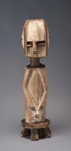 Mbete - Half-figure of a man on a prestige stool Date: 19th–20th century Location: Not on display Century: 19th Century AD Media: Wood, Pigment, Cowry Shells, Fiber And Metal Dimensions: 28 1/2 x 7 1/2 x 7 in.