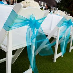 Chairs are adorned with a turquoise chiffon ribbon