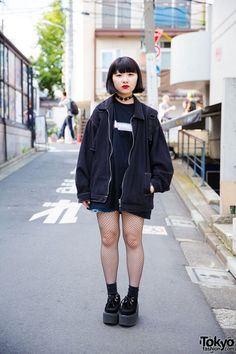 Mo-Chi was wearing black from head to toe in resale fashion, with only her red lips for color. She wore a black t-shirt, shorts, and a zipper jacket. She finished her look with black socks over fishnet stockings and black platform creepers from Nadia. She carried a black backpack and accessorized with a Nadia leather collar.