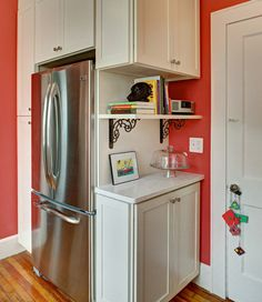 I love the color of this kitchen and the way they built shelves around the fridge.
