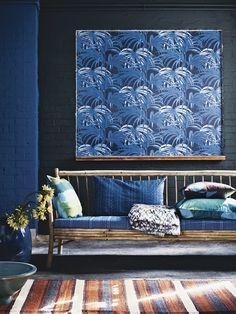 A large panel of framed wallpaper with a modern palm motif makes a striking focal point above a bamboo sofa in this living room. Rich indigo blue is a strong trend in interiors. Bamboo lounge couch (with white seat cushion), €675, Tine K Home, tinekhome.com. Palmeral wallpaper in Midnight/Azure H401/4, £148 a roll, House of Hackney, www.houseofhackney.com. Styled by Melanie Molesworth; photographed by Emma Lee. Homes & Gardens, July 2014.
