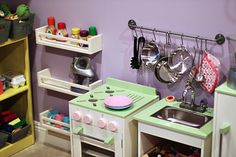 Cute play kitchen/market/cafe space complete with awning, scale, and lots of storage (Ikea spice racks and bar; added bins to repurposed old bookcase)