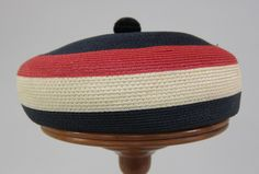 Multi-colored straw hat | Label: Asbury Millinery Co. (Dallas, Texas) | United States, 1952 | . Based on a beret, the hat consists of a crown of finely woven straw in bands of dark blue, red, white, and dark blue | The crown is formed as a flattened sphere, surmounted by a small sphere of dark blue velvet | University of North Texas