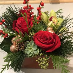 A masculine Holiday texture box with roses, Cybmidium orchids, Ilex, succulents, seeded Eucalyptus, Princess Pine and cedar accented with glass balls.
