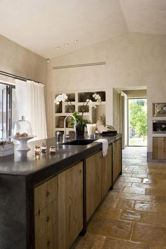 Cucina rustica in cemento e legno con il pavimento in cotto