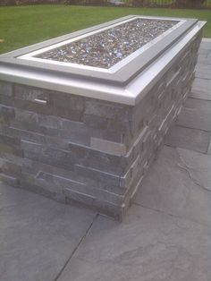 Raised gas fire pit with crushed glass, stone cladding and stainless steel cap.
