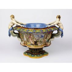 This wine cooler, depicting bacchanalian scenes, shows Minton's popular majolica technique. Majolica was similar to the Italian renaissance maiolica which inspired it; made from earthenware and covered in an opaque white glaze which was then painted freehand, often in styles which echoed or copied original Italian examples. Richly coloured and elaborately modelled, majolica wares complemented the bold use of colour in nineteenth century domestic interiors and came to epitomise high-Victorian…