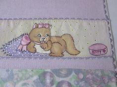 Detalhe da faixa pintada a mão, da fralda de boca lilás, com motivo 'gatinha dengosa'.