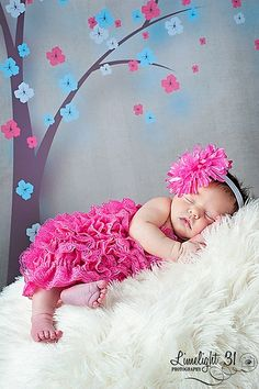 newborn baby girl photography.  Use wall decorations as a prop.  Just great.
