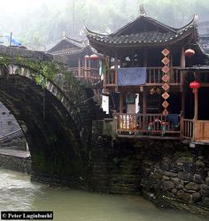 An traditional Chinese residence with verandahs by an arch bridge in southern China
