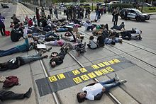 "Protesters lying down over rail tracks with a ""Black Lives Matter"" banner."