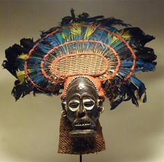 Africa | Chihongo mask from Chokwe people.  D.R. Congo, Angola or Zambia. | Mid 20th century | Wood, rope, metal, raffia, paint, cloth, beads, feathers
