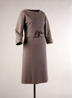 Designer: Hubert de Givenchy (French, b. 1927)  Givenchy Boutique (French, established 1952)  Place Made: France  Date Made: ca. 1959  Medium: Double-knit wool, silk  Dress and overblouse in slate gray wool jersey with bow at waist.  The overblouse, made popular in America by Jacqueline Kennedy, has a neckline that was cut to stand up and away from the shoulder blades and a deep bias band at the hem that impedes its fall.
