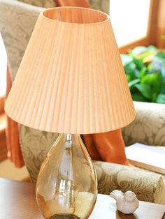 Wrap It with Ribbon---Ribbon wrapped around a plain paper shade creates the look of pleated silk. To keep this project affordable, we hit the clearance bin and found four 8-yard ribbon spools. Use fabric tape to secure a ribbon end (and subsequent ends) to the inside of the shade. Wind ribbon around the shade, overlapping more at the top than at the bottom if using a tapered shade.