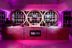 The bar design was inspired by the collection, using its graphic print on the front with gold circles behind the bar that recalled the eye shadow and blush palettes. Gold glitter champagne bottles customized for the event rounded out the display.