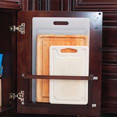 Cutting board holder that hides behind a base cabinet door