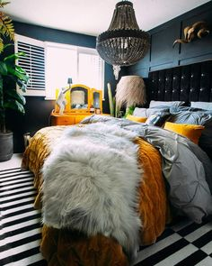 This fabulous dark decor bedroom has splashes of colour with the yellow chunky knit and sheepskin throw. All pulled together with a beautiful black beaded chandelier