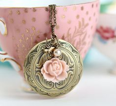 A vintage inspired brass finish large round locket with scroll designs on the front and back. A pretty pale pink resin flower adorns the front of the locket.  Above the locket hangs a small pale glass pearl and a brass bird charm.