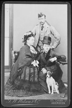 Queen Victoria with Princess Beatrice and Prince Arthur, 1878   Portrait photograph of Queen Victoria (1819-1901) with Princess Beatrice (1857–1944) and Prince Arthur (1850-1942). The Queen and Princess Beatrice are seated. There is a terrier dog sitting in front of Princess Beatrice and Prince Arthur is standing at the back wearing a highland uniform