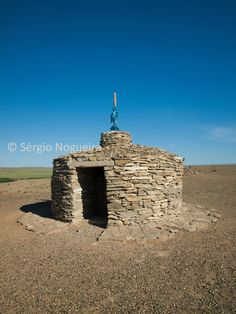 Stone Ovoo in Mandal-Ovoo in the Gobi desert  A stone mound, or ovoo, in Mongolia marks a place where spirits are said to have appeared; respectful travelers circle it three times.