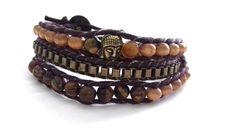 Pulseira estilo Chan Luu com 3 voltas, contas de madeiras, olho de tigre e corrente ouro velho. O fecho é com um moderno botão e possui duas regulagens de tamanho. Feito com fio de algodão marrom.
