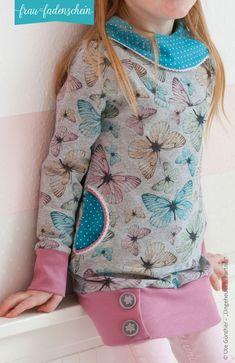"""""""Lottchen"""" ist die Kinderversion des Dampenpullovers und-kleides Lotte. Der besondere Hingucker an diesem Schnitt ist der asymmetrische Wickelkragen mit Knopfleiste. Hier kannst du deiner Fantasie freien Lauf lassen: verwende normale Knöpfe, Druckknöpfe, Knebelknöpfe – alles ist möglich und deine Wahl verleiht deinem neuen Pullover oder Kleid einen ganz individuellen Look. Die Knopfleiste wiederholt sich auch im Saumbund des Pullovers oder Kleides. Du kannst hier aber auch ein ganz normales…"""