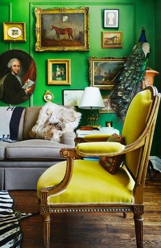 Mustard mohair chair in green living room with gallery wall of portraits and paintings.