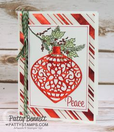 Create a handmade Christmas Card with red foil accents, using the Stampin Up! delicate ornaments dies and red striped vellum paper background. Stamp the holly sprig using the Peaceful Wreath stamp set. Color in with Blender Pens.  Card by Patty Bennett
