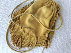 Hand stitched turquoise handle on fringe cross body drawstring bag. By XOM