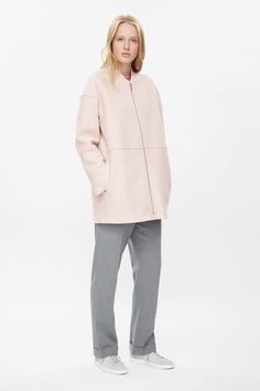 A long straight shape, this zip-up coat is made from softly structured boiled wool with modern raw-cut edges. Smooth on the inside, it has a raised collar, front pockets and a modern zip fastening along the front.