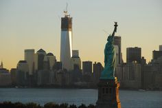 One World Trade Center holding head high next to Statue of Liberty