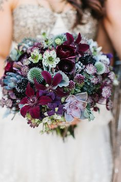 Deep burgundy adds richness to this textural bouquet of clematis, scabiosa, succulents, echinops, allium, dusty miller, and silver brunia.
