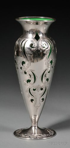 "European Furniture & Decorative Arts | F - Sale 2566B - Lot 351A    Alvin Sterling Overlay Green Glass Vase, early 20th century, emerald green glass tapering ovoid body with short everted neck and spreading foot, with pierced and acanthus-engraved sterling overlay, ht. 10 in.   Estimate $400-600     small, stable chip to underside edge of foot (approx. 1/4""), light ding to one silver cartouche at body; minor age wear."