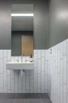 bathroom. long subway tile, vertical running bond, chair rail - Bicycle Haüs / Debartolo Architects