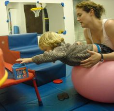 Moving toys from floor into container promotes neck & back strength, reaching, eye-hand coordination. j