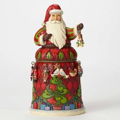 Santa is wearing a blue hat. His Santa suit is red and highly decorated with red as the back ground. Santa is wearing green gloves and is holding an ark that