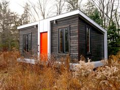 FARM HOUSE: This tiny house on wheels was built by Yestermorrow School students, and features a charred wood exterior and cool orange door. There's plenty of light shining though its front and side windows. Tiny House Cabin, Tiny House On Wheels, Farm House, Small Room Design, Tiny House Design, Tiny House Exterior, Orange Door, Micro House, Tiny House Movement