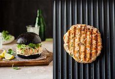 salmon burger on a black brioche bun