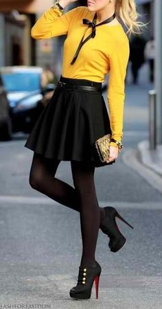 Yellow top, black skirt, opaque black tights and military inspired high heels.