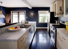White Carrera Marble, Cream cabinets and Navy blue walls define this trendy kitchen