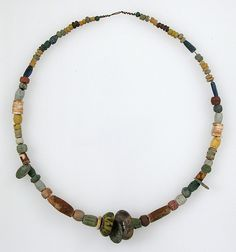 Beaded Necklace Date: 500–600 Geography: Made in Niederbreisig, Germany Culture: Frankish Medium: Glass, stone, shell, amber, 3 copper alloy coins. Classification: Glass-Beads