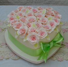 A romantic heart shaped single tiered wedding cake filled with romantic flowers for a spring colour scheme.