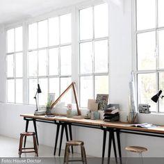 Praktisch und dekorativ: Hier wurden mehrere Schreibtische im Werkbank-Look zu einer großzügigen Arbeitsfläche kombiniert. Durch die Fensterfront fällt viel…